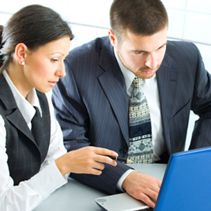 two people looking at a computer screen, where it appears as if one is instructing the other